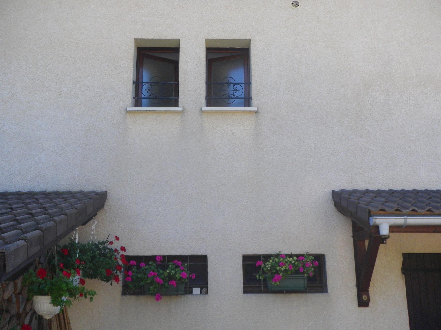 Grille de défense réalisée avec nos décors rosette volutes et supports pour barreaux . Localisation Savoie