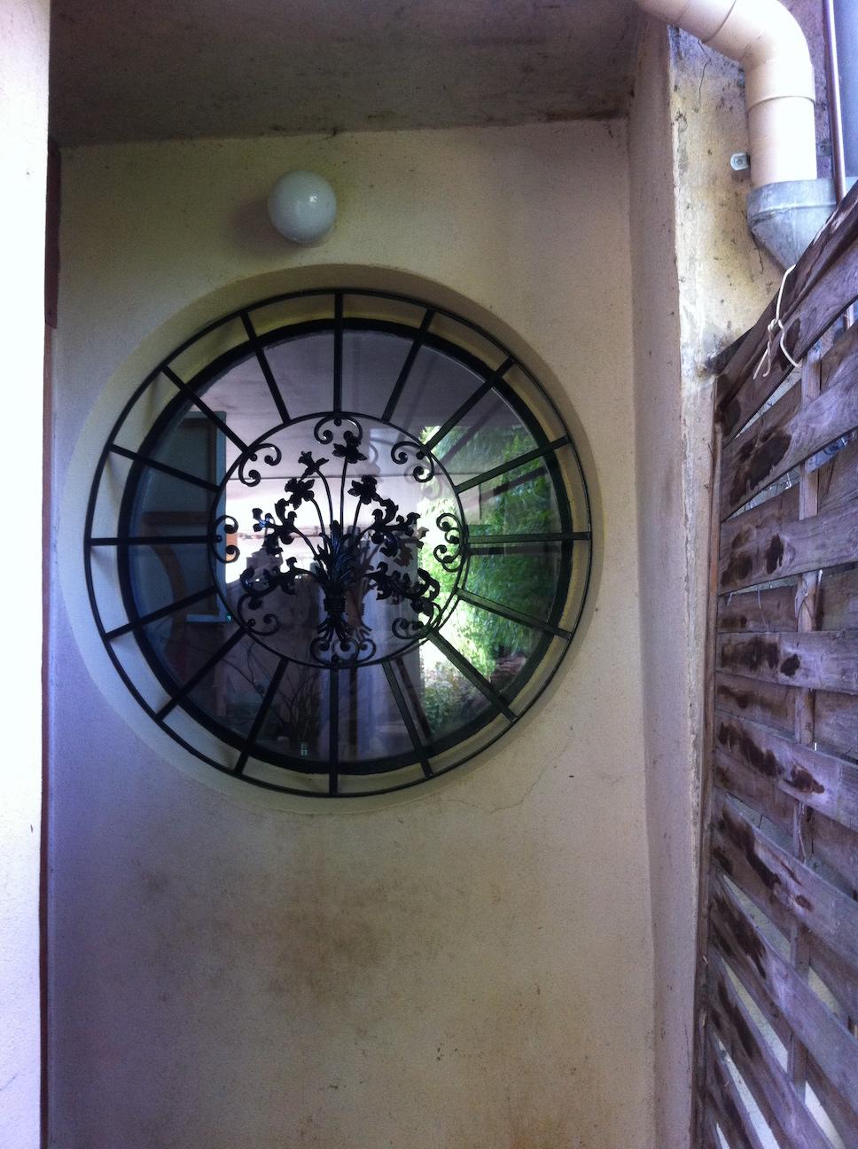 Conception et fabrication complete par notre client d'une grille type oeil de boeuf en fer forgé -  Réalisation a  partir de notre gamme de pieces detachees.