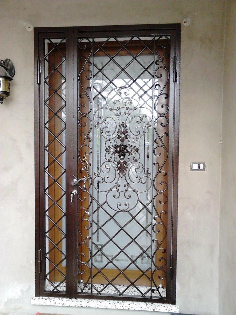 Conception et fabrication complète par client d'une porte grille de protection en fer forgé avec décors  de notre gamme de pièces détachées .