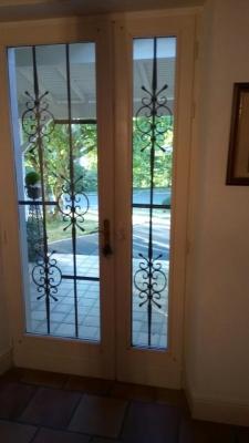 Création et fabrication complète par notre client d'une grille de protection sur porte en bois et verre  . Réalisation à partir de notre gamme de pièces détachées. Localisation Vendée